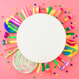 Blank white frame over party accessories and candies on pink surface