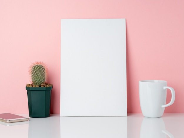 Blank white frame and plant cactus, cup of coffee or tea on a white table against the pink wall