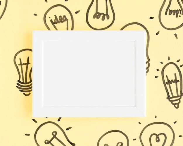 黄色の背景に電球と空白の白いフレーム