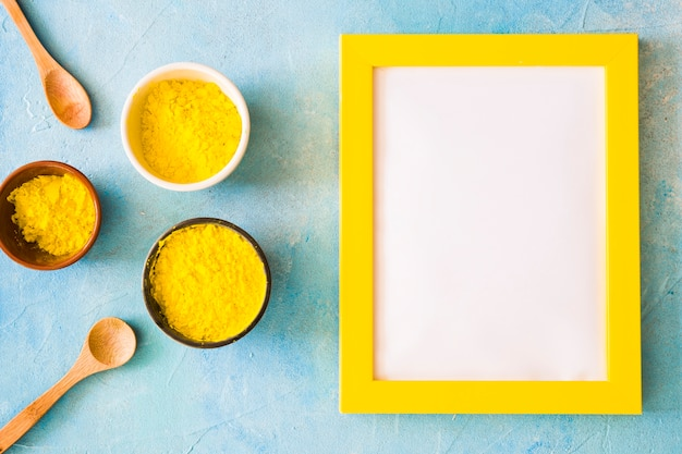 Blank white frame with yellow border near the holi color powder on concrete backdrop