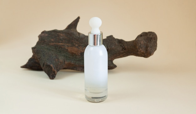 Blank white glass serum bottle for cosmetic products on beige background