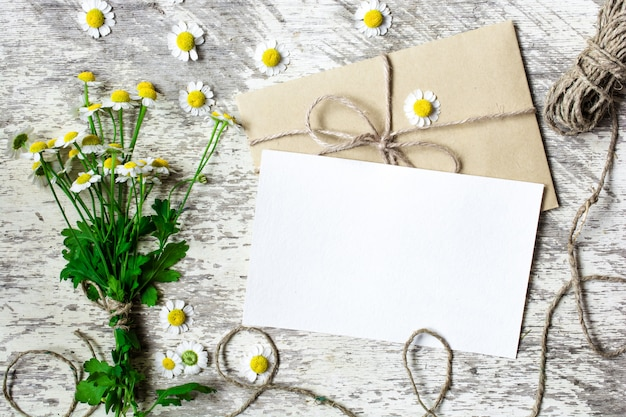 Blank white greeting card and envelope with chamomile flowers