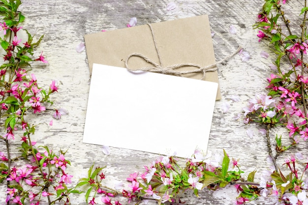 Blank white greeting card and envelope with spring blossoming branches of sakura and cherry flowers