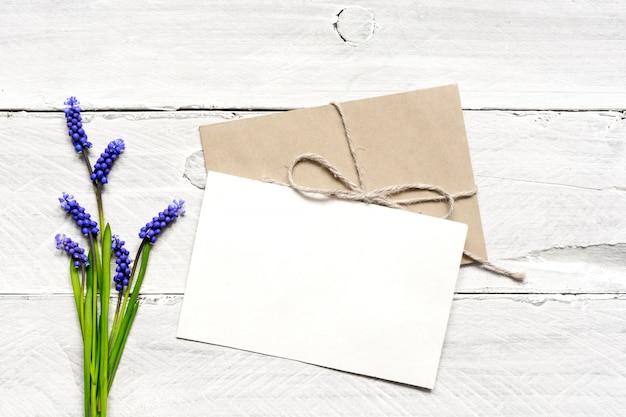 Blank white greeting card and envelope with spring blue flowers bouquet