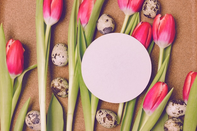 Blank white greeting card on pink tulips and quail eggs