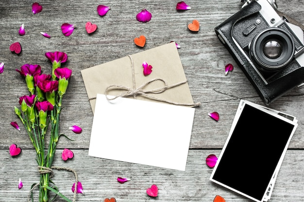 Blank white greeting card with blank photo and retro camera with flowers