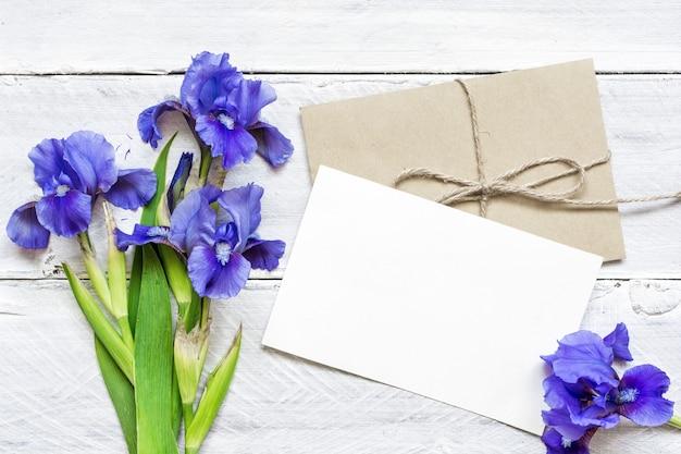 Пустая белая открытка с голубыми ирисами букет и конверт