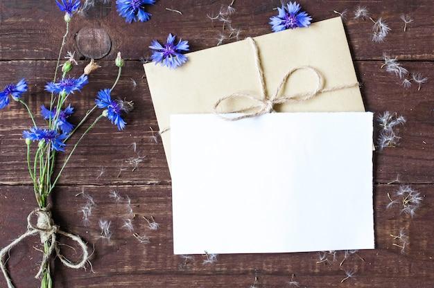 Пустая белая открытка с васильками и семенами одуванчика