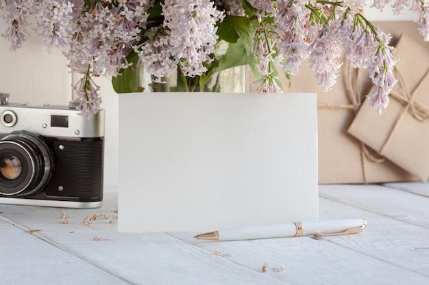 Пустая белая открытка с букетом цветов сирени.