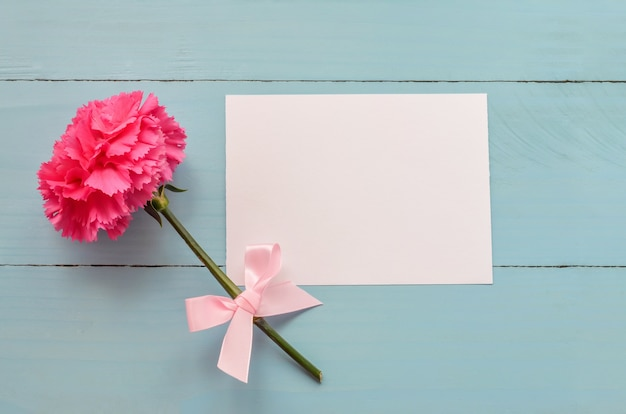 Blank white greeting card with pink carnation flower