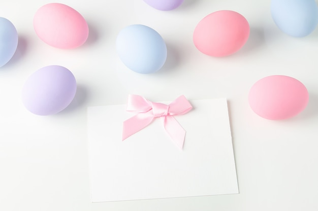 Blank white greeting card with pink ribbon bow and pastel easter eggs