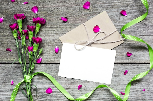 Blank white greeting card with purple carnation flowers