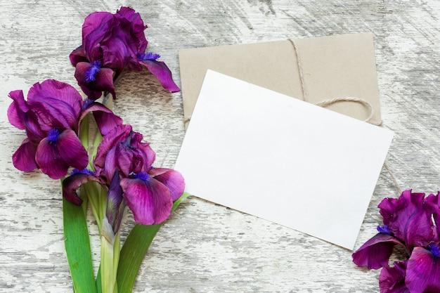 Пустая белая открытка с фиолетовыми ирисами букет и конверт