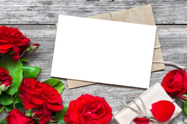 Пустая белая открытка с букетом красных роз и конверт с подарочной коробкой
