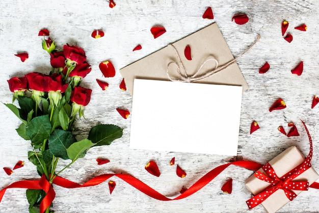 赤いバラのブーケと空白の白いグリーティングカード