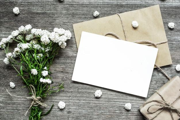 白い花の花束とギフトボックスと芽の封筒と空白の白いグリーティングカード