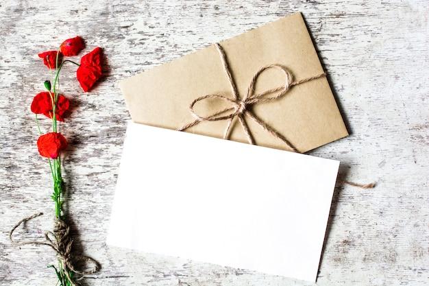 Пустая белая открытка с полевыми цветами красного мака