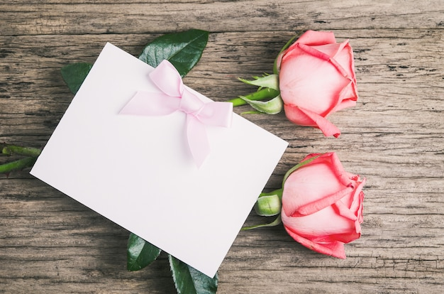 Blank white greeting paper card with pink roses and ribbon