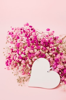 Blank white heart shape with baby's-breath flowers on pink background
