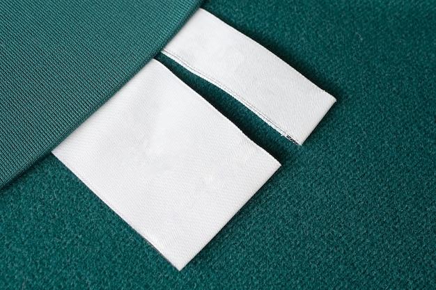 녹색 패브릭 질감 배경에 빈 흰색 세탁 관리 옷 레이블
