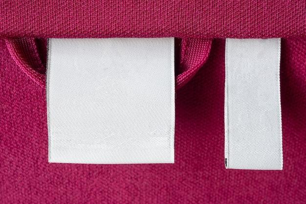 빨간색 패브릭 질감 배경에 빈 흰색 세탁 관리 옷 레이블
