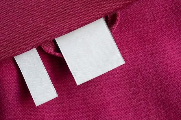 Пустая белая этикетка для одежды по уходу за стиркой на фоне текстуры красной ткани