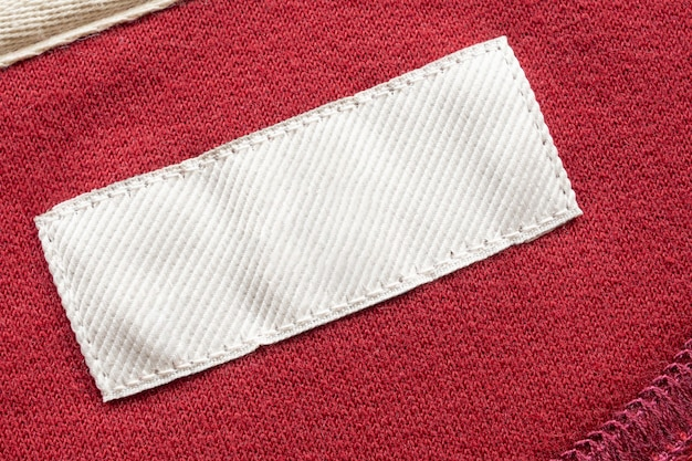 빨간색 패브릭 질감 배경에 빈 흰색 세탁 관리 의류 레이블