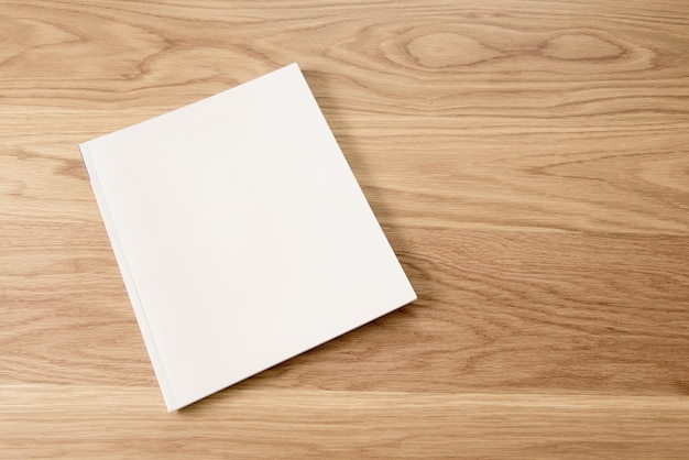 나무 테이블 배경에 빈 흰색 잡지 표지입니다.