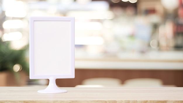空白の白いメニューボードは、木製のテーブルに立って