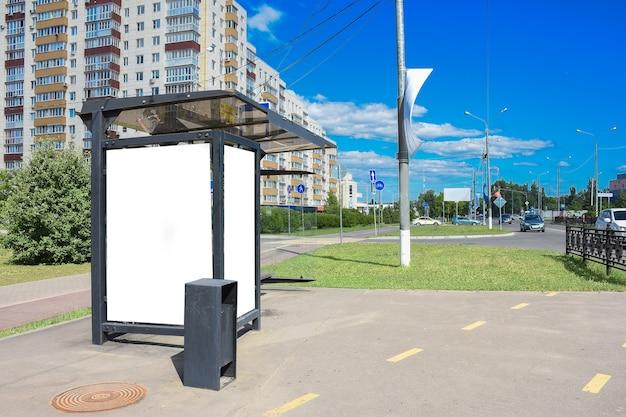 あなたの広告のための夏の日の場所のバス停で空白の白いモックアップ垂直看板