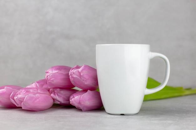 Макет пустой белой кружки с розовыми тюльпанами