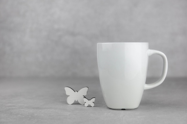 Blank white mug mockup with white butterfly on light gray concrete stone surface