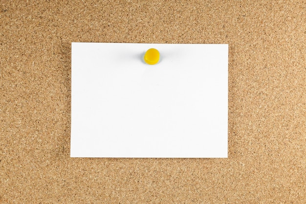 Blank white note papers is pinned to a cork board.