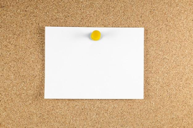 空白の白いメモ用紙がコルク板に固定されています。