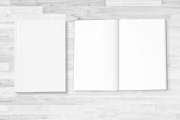 흰색 나무 테이블에 열린 노트북 페이지와 빈 흰색 노트북 커버.