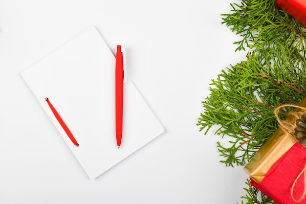 Blank white notebook and red pen on christmas white space. christmas fir branches, cones, gifts. letter to santa claus, mock up. blank white notebook and red pen on white.