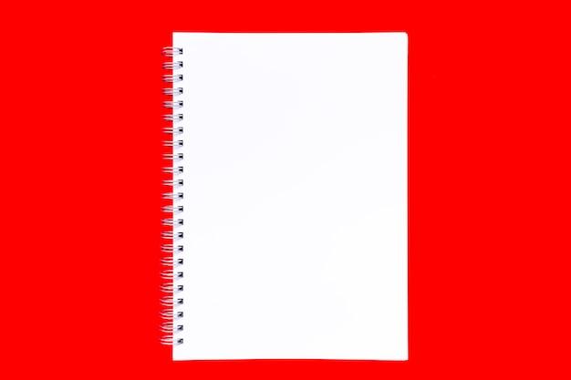 真っ赤な背景にらせん状の空白の白いノートブックシート。