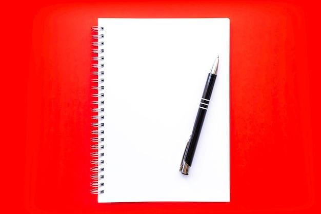 Пустой белый лист тетради со спиралью на простом красном фоне.