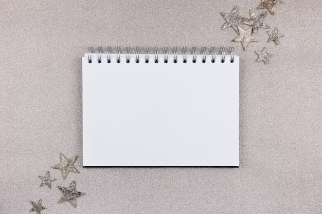 Blank white notebook with christmas decoration on shiny sparkling background