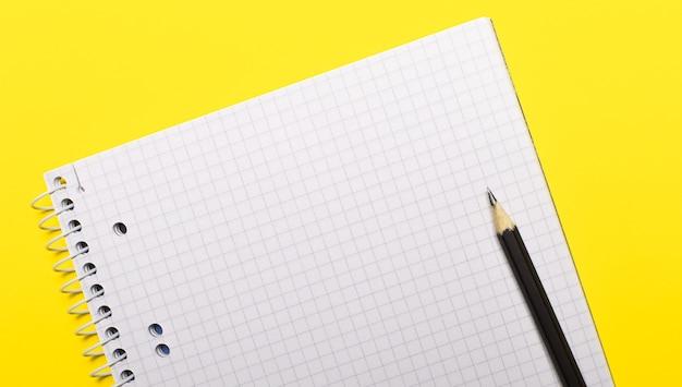 明るい黄色の背景にテキストと黒の鉛筆を挿入する場所と空白の白いノート