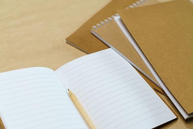 종이 배경의 빈 흰색 메모장과 연필은 위쪽 보기 복사 공간을 조롱합니다.