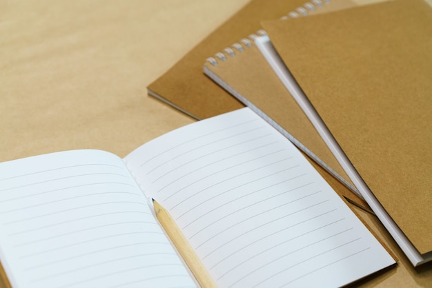 Blank white notepad and pencil on paper background mock up top view copy space