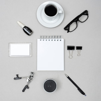 Blank white notepad surrounded by coffee cup; nail varnish; eyelash curler; speaker; pen and paper clips above gray background