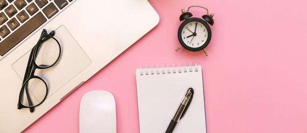 Пустой белый блокнот с офисными и личными аксессуарами, черный будильник и очки на розовом backg ...