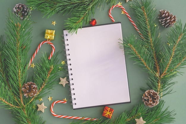 Blank white open notebook with a pen on a christmas background made of trees, toys and christmas candies