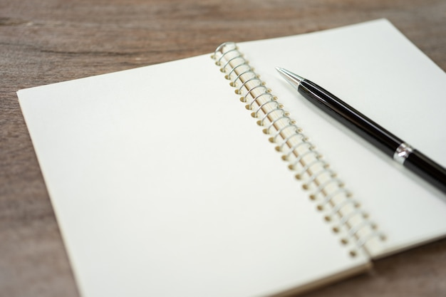 Blank white open notebook with pen
