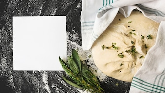 Blank white page and raw dough with rosemary on kitchen worktop