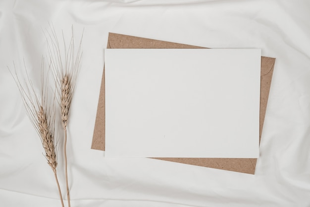 Blank white paper on brown paper envelope with barley dry flower on white cloth
