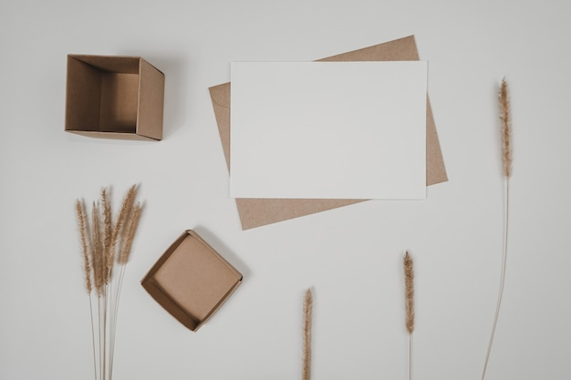 Blank white paper on brown paper envelope with bristly foxtail dry flower and carton box. mock-up of horizontal blank greeting card. top view of craft  envelope on white background.