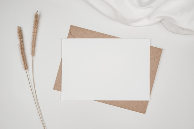 Blank white paper on brown paper envelope with bristly foxtail dry flower and white cloth
